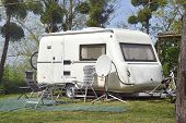 image of caravan  - White caravan with arm chairs and satellite dish at the camping - JPG