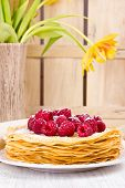 French Crepes with fresh raspberries and powder sugar (selective focus)