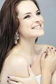 Portrait of a beautiful happy brunette woman touching shoulders. Long loose hair against gray background. Purple manicure on nails