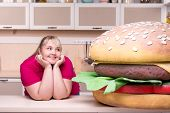 Smiling overweight woman and huge hamburger
