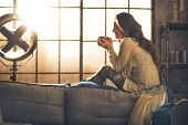 Young Woman Enjoying Cup Of Hot Beverage In Loft Apartment