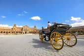 SEVILLE, SPAIN - OCTOBER 11, 2014: A horse drawn carriage tour through Spanish Square. The Horse drawn carriages are a popular way for tourists to visit the city.