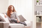 Red Headed Very Cute Girl Serious On Her Sofa