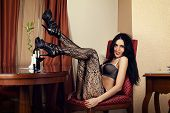 luxurious woman sitting in a chair in lingerie