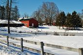 A Snowy Barn On A Farm With A Wooden Fence