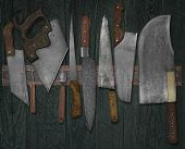 vintage set of knives on the magnet rack against wall, faded colors