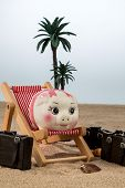 a piggy bank is in a deck chair. symbol photo for airline travel and expenses on vacation