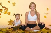 Woman And Child Doing Yoga Under The Leaves
