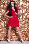 picture of leggy  - Young leggy brunette wearing red dress posing on golden background - JPG