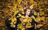 Nice girl covered with autumnal leaves. Young woman laying down on the ground covered by foliage