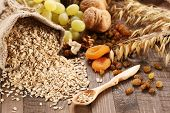Oatmeal In A Sac, Ears Of Oats, Dried Apricots, Raisins, Grapes, Nuts On The Background Of Wooden Pl