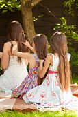 Girls Sitting On Grass At Garden And Doing Hairstyles