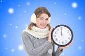 Happy Beautiful Woman In Winter Clothes Holding Office Clock Over Blue Winter Background
