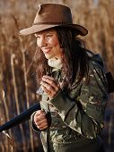 stock photo of shotgun  - Waterfowl hunting smiling female hunter carry a shotgun and she use a duck call shore and reeds on background - JPG