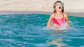 young child girl snorkelling in mask on tropical beach background