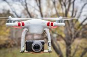 FORT COLLINS, CO, USA, November 2, 2014:  Airborne radio controlled DJI Phantom 2 quadcopter drone flying with  the Panasonic Lumix GM1 camera mounted on a home made platform, blurred tree background.