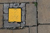 Yellow Square Gas Lid On Street Cigarette Butts