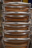 Stacked Aluminium Silver Chairs Outside A Cafe