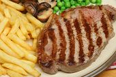 Sirloin steak dinner with fries peas and mushrooms.
