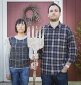 Fun Mixed Race Couple Portrait Simulating the American Gothic Painting by Grant Wood.
