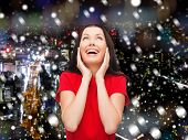 christmas, holidays, celebration and people concept - smiling woman in red dress over snowy night city background