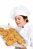 Pretty, mature female chef in her uniform, inhaling the aroma of a tray of her fresh baked chocolate chip cookies.  Isolated on white background