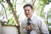 Businessman suffering chest or stomach pain related to heart attack, angina, or other illenss like flu or ebola.