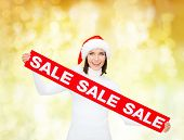 sale, shopping, christmas, holidays and people concept - smiling woman in santa helper hat with red sale sign over yellow lights background