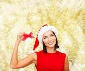 christmas, holidays, winter, happiness and people concept - smiling woman in santa helper hat with jingle bells over yellow lights background