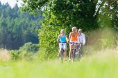 Parents and daughter have bicycle or bike tour on country lane
