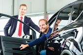 image of showrooms  - Seller or car salesman and client or customer in car dealership presenting the interior decoration of new and used cars in the showroom - JPG