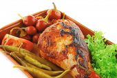 chicken drumstick with tomato and green peppers on white