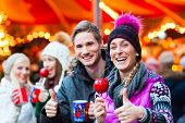 Friends drinking mulled wine and eating crystalized apples on German Christmas Market