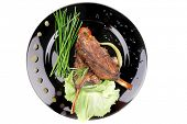 meat savory: roast ribs on black plate with peppers and chives