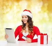 christmas, holidays, technology and shopping concept - smiling woman in santa helper hat with gift box, credit card and tablet pc computer over yellow lights background