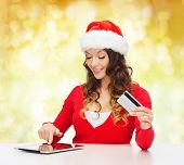christmas, holidays, technology and shopping concept - smiling woman in santa helper hat with credit card and tablet pc computer over yellow lights background