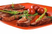 red meat slices and vegetables on red plate