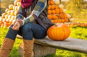 Closeup On Happy Young Woman Sitting With Pumpkin In Front Of Pu