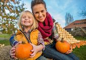 Portrait Of Smiling Mother And Child Sitting On Haystack With Pumpkins