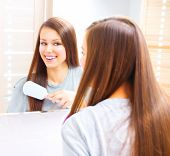 Beautiful smiling teenage girl is combing her long silky hair after getting up in the morning. Young attractive happy woman is brushing her brown hair enjoying them in the mirror and admiring herself