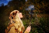Beautiful young woman outdoor on autumn day holding burning torch