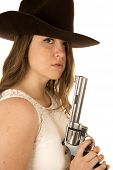 foto of pistols  - Cowgirl staring at camera holding large pistol - JPG