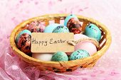 image of bird egg  - Bird colorful eggs in wicker basket on bright background - JPG