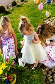 foto of easter eggs bunny  - Children on an Easter Egg hunt on a meadow in spring - JPG