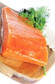 picture of redfish  - single pink salmon bit on a big wooden dish with white cheese - JPG