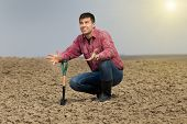 picture of shovel  - Desperate farmer holding shovel on farmland and looking in sky - JPG