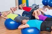 picture of bending over backwards  - Fit people stretching on exercise balls in fitness club - JPG