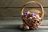 stock photo of bird egg  - Bird eggs in wicker basket with decorative flowers on wooden background - JPG