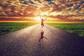 Happy woman jumping on long straight road, way towards sunset sun. Travel, happiness, win, healthy l poster