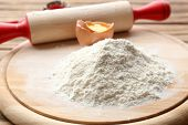 picture of plunger  - Heap of flour on cutting board with egg and plunger on wooden table - JPG